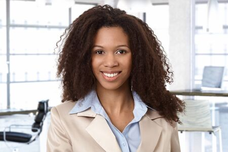 Portrait of attractive afro woman at office, looking at camera, smiling. photo
