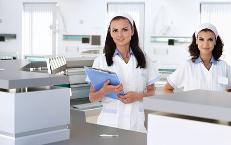 Young health care workers at hospital reception smiling. Stock Photo - 26368754