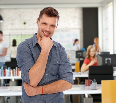 Happy young casual man at trendy youthful office. photo