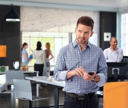 モダンなスタイリッシュなオフィスで携帯電話を使用してカジュアルな実業家笑みを浮かべてします。