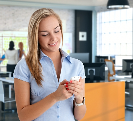 socializing: Female office worker using cellphone at office, chatting and social networking.