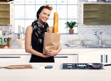 gingerish: Trendy young woman in kitchen with shopping bag full of food.