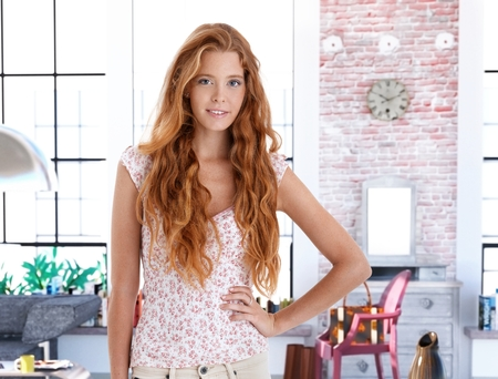 Smiling redhead woman posing for portrait at home. photo