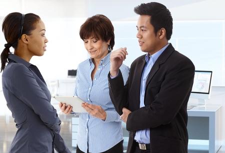 Diverse Business-Gruppe arbeiten zusammen mit Diskussion im Büro.