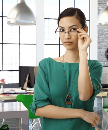 officeworker: Asian female officeworker at office wearing green blouse standing and raising glasses.
