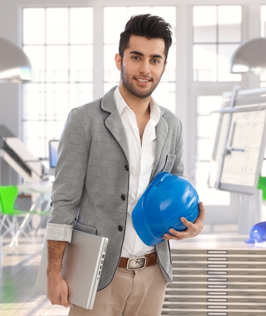 Middle-eastern architect leaving office, carrying laptop and protective helmet. photo
