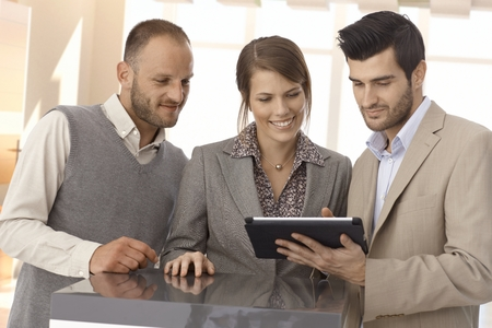 Happy business partners standing at table looking at tablet in office. photo