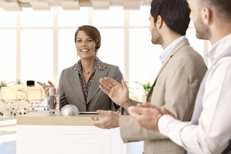 demo: Formal speech at pulpit on business conference presented by successful businesswoman, colleagues clapping. Stock Photo