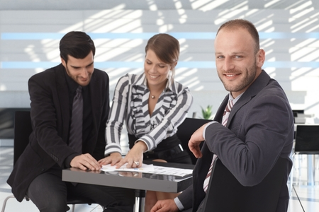 Business meeting at coffee table, happy business people working together. Stock Photo - 26739084