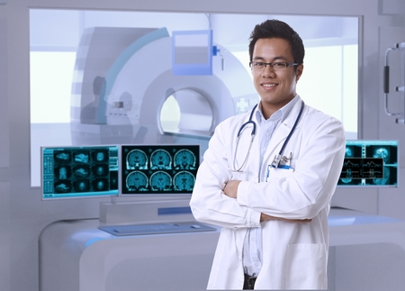 Portrait of asian doctor in MRI room at hospital, looking at camera, smiling. Stock Photo