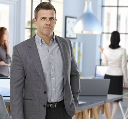Goodlooking middle aged caucasian man in jacket standing at office. Stock Photo - 26739089