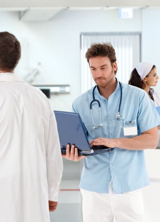 Young doctor with laptop, people working in hospital. Stock Photo - 26739091