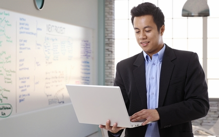 markerboard: Asian businessman working with laptop in board room at office, smiling. Stock Photo