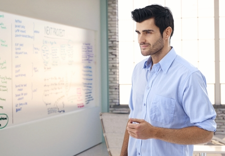 Caucasian male officeworker thinking in whiteboard room of office, smiling. photo