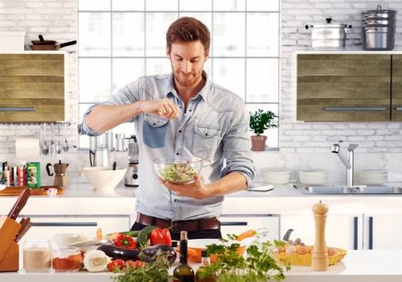 Hombre hermoso que cocina en casa preparando la ensalada en la cocina. Foto de archivo