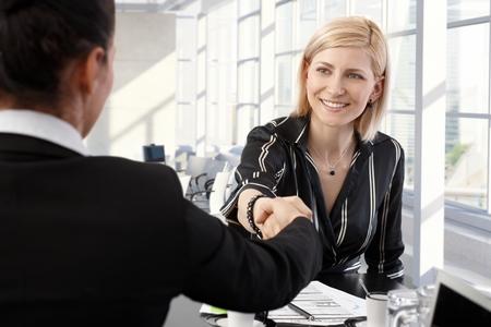 Lächelnde Geschäftsfrauen Händeschütteln im Büro Tagungsraum.