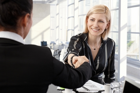 Smiling businesswomen shaking hands at office meeting room. Stock Photo