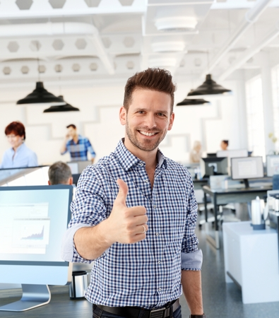 Happy casual man showing thumb-up in office, smiling. photo