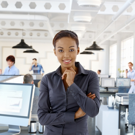 Portrait of happy black female office worker in office with working people. photo