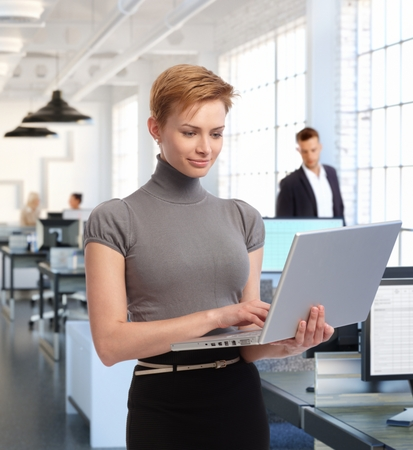 gingerish: Businesswoman working with laptop at office, standing, smiling.