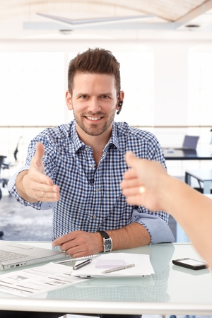 advising: People shaking hand over office desk, casual businessman smiling.