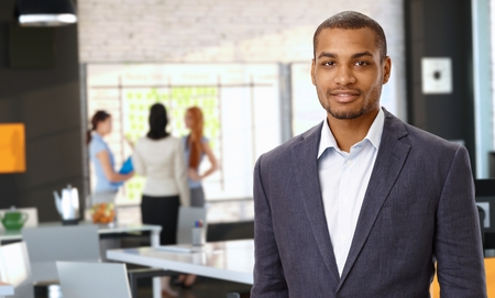 Portrait of casual black businessman at office, wearing jacket looking at camera, confident.