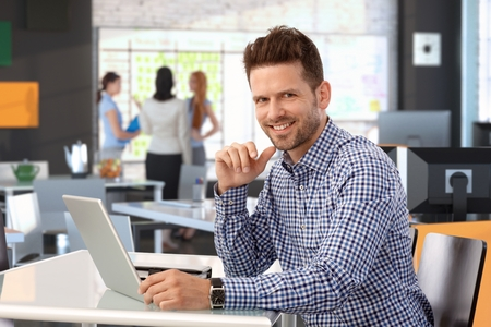 Casual businessman working with laptop computer at office desk, looking at camera, smiling.