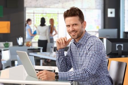 Casual zakenman werken met laptop computer op kantoor, kijken naar camera, lachend. Stockfoto - 26739208