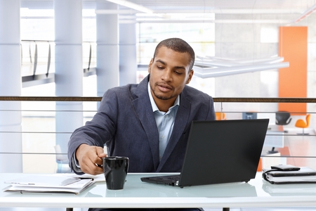 Casual black businessman working with laptop computer at office desk. photo