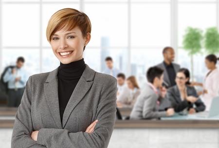 gingerish: Empresaria feliz en oficina personas que trabajan en segundo plano. Foto de archivo