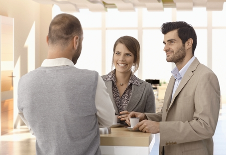 Happy business people standing at coffee table at office, talking. Stock Photo - 26978183