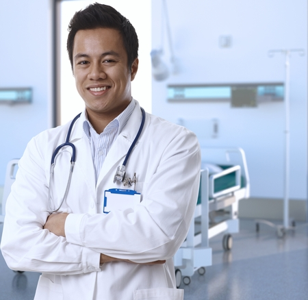 Portrait of happy asian doctor in lab coat standing at hospital room, smiling. photo