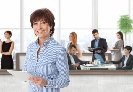 Happy Senior Geschäftsfrau mit Team der Geschäftsleute im Büro arbeiten.