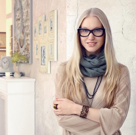 Attraktive kaukasisch Casual junge blonde noblen Innendesigner mit Brille am Weinlese Hause. Stehen, Lächeln, verschränkten Armen, Blick in die Kamera.