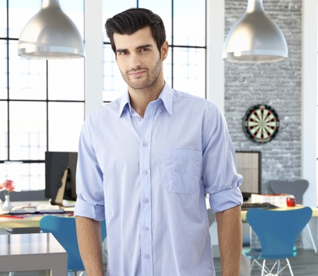 officeworker: Portrait of young caucasian male officeworker at creative office space. Stock Photo