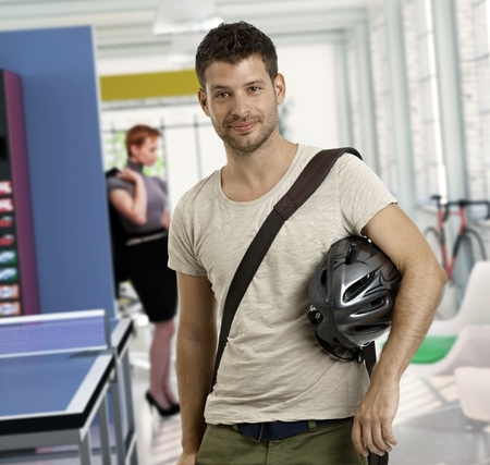 arriving: Casual young man at office arriving to work by bicycle. Stock Photo
