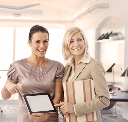 Happy businesswomen at office showing tablet, blank screen photo