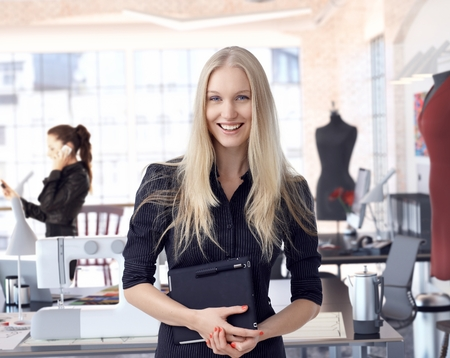 jovenes empresarios: Feliz empresario de la moda femenina del dise�ador en el estudio creativo que lleva la peque�a empresa. Empresaria que sostiene la tablilla, sonriendo.
