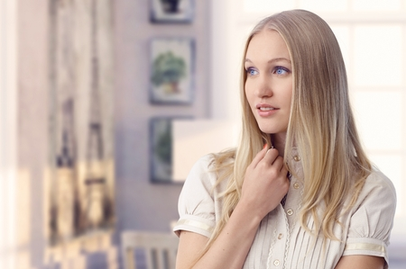 dreamy eyed: Beautiful young blonde casual blue eyed caucasian romantic woman daydreaming at retro home. Wondering, thinking. Copyspace. Stock Photo