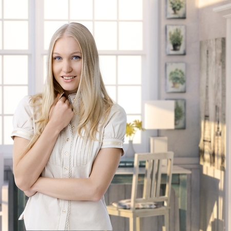 blue eyed: Attractive casual young blue eyed caucasian blonde woman standing at retro home. Smiling, looking at camera.