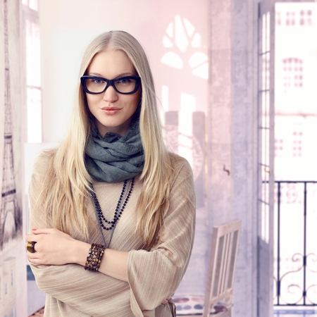 scandinavian people: Young trendy casual caucasian blonde woman with glasses at retro home. Standing, arms crossed, smiling looking at camera. Wearing jewelry, copyspace.