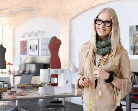 Portrait of happy casual trendy caucasian blonde fashion designer businesswoman at studio. Smiling, standing, looking at camera.