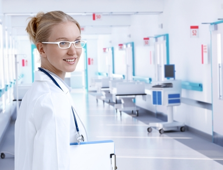 scandinavian people: Happy young caucasian blonde female doctor standing at at hospital hallway. Lab coat, stethoscope, clipboard, wearing glasses, smiling. Copyspace.
