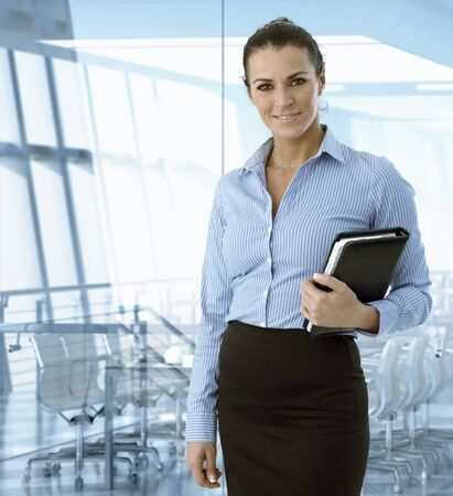 table skirt: Executive caucasian businesswoman standing in front of meeting room, smiling. Stock Photo