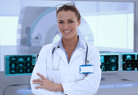 Portrait of mid-adult female doctor in MRI room at hospital, looking at camera, smiling. Imagens