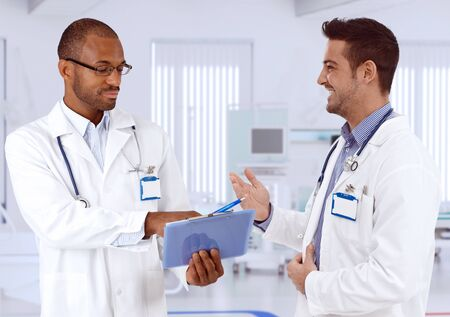 Male doctors consulting at hospital corridor, smiling. Stock Photo - 27297449