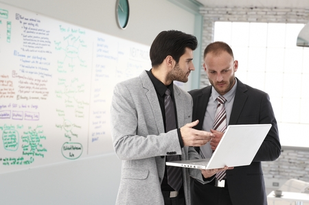 markerboard: Businessmen planning, looking at laptop at office in front of a huge whiteboard. Stock Photo