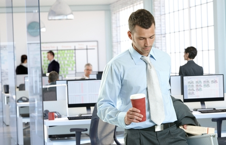 Businessman arriving to office holding coffee to go. Stock Photo - 27297466