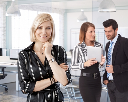 Businesswoman in front at office with working colleagues in background. Stock Photo - 27297468