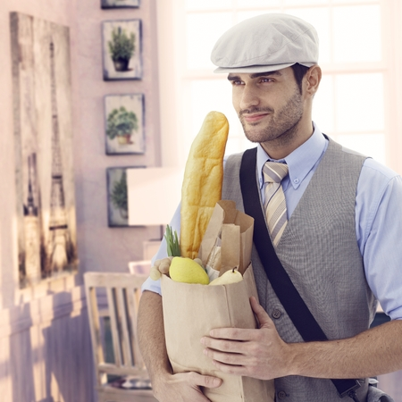 Handsome casual caucasian man holding grocery bag at vintage Paris home. Smiling, cap and french baguette bread, bristly. photo
